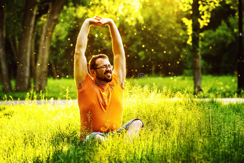 Een gelukkige mens rekt zich op groen gras met squint oog uit royalty-vrije stock foto