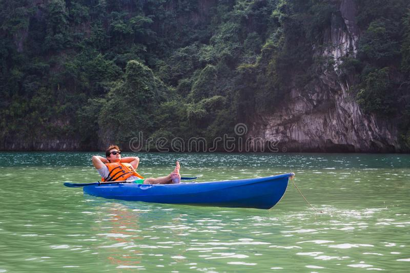 Een gelukkige mensenzitting in een kajakboot op meer het ontspannen royalty-vrije stock foto's
