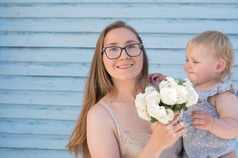 Een gelukkige moeder en dochterpeuter snuift een klein boeket van witte bloemen tegen een blauw planked muur Scène van liefde, stock afbeelding