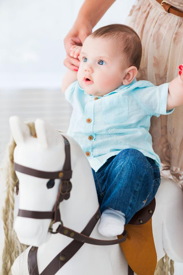 Een gelukkige moeder helpt een kleine zoon om een stuk speelgoed paard op te zetten stock foto