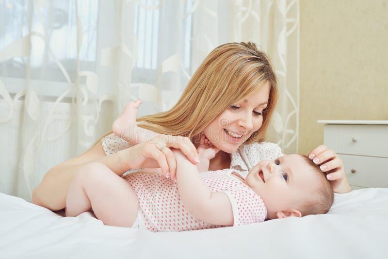 Een gelukkige moeder met een baby speelt op een bed stock fotografie