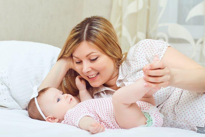 Een gelukkige moeder met een baby speelt op een bed stock foto's