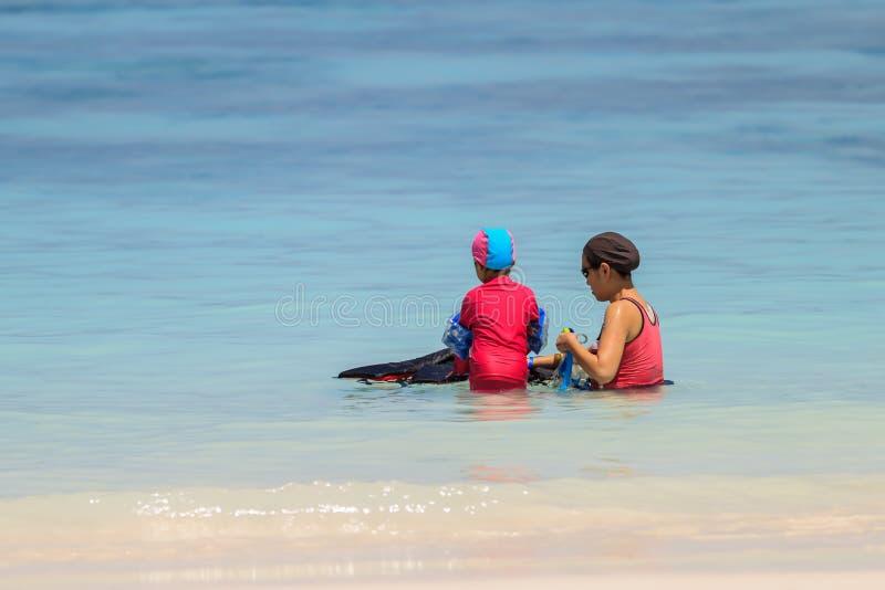Een gelukkige moeder met haar kind die met materiaal snorkelen stock afbeeldingen
