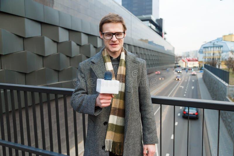 Een gelukkige verslaggever leidt een rapport over de camera op de straat royalty-vrije stock afbeeldingen