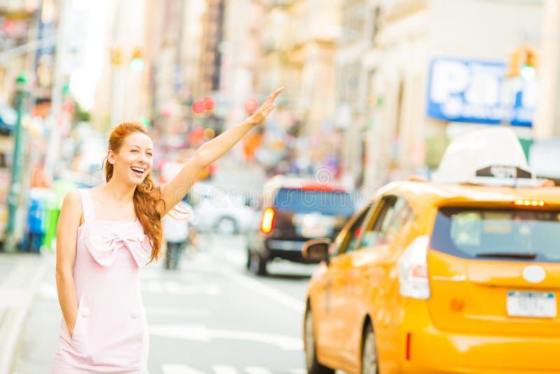 Een gelukkige vrouw die een gele taxi begroeten terwijl het lopen op een straat in de stad van New York stock foto