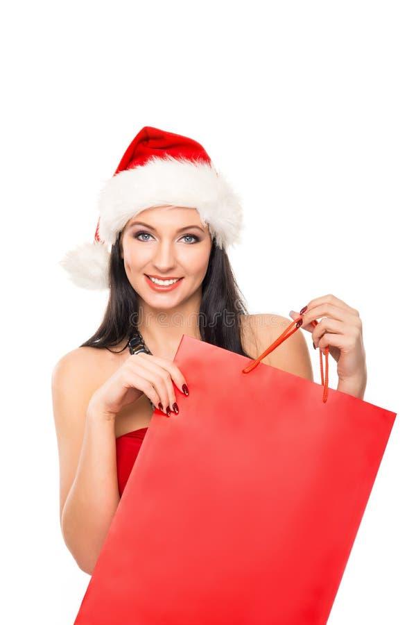 Een gelukkige vrouw in een Kerstmishoed die een rode zak houden royalty-vrije stock foto