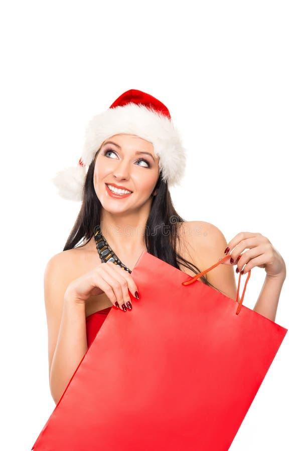 Een gelukkige vrouw in een Kerstmishoed die een rode zak houden royalty-vrije stock afbeeldingen