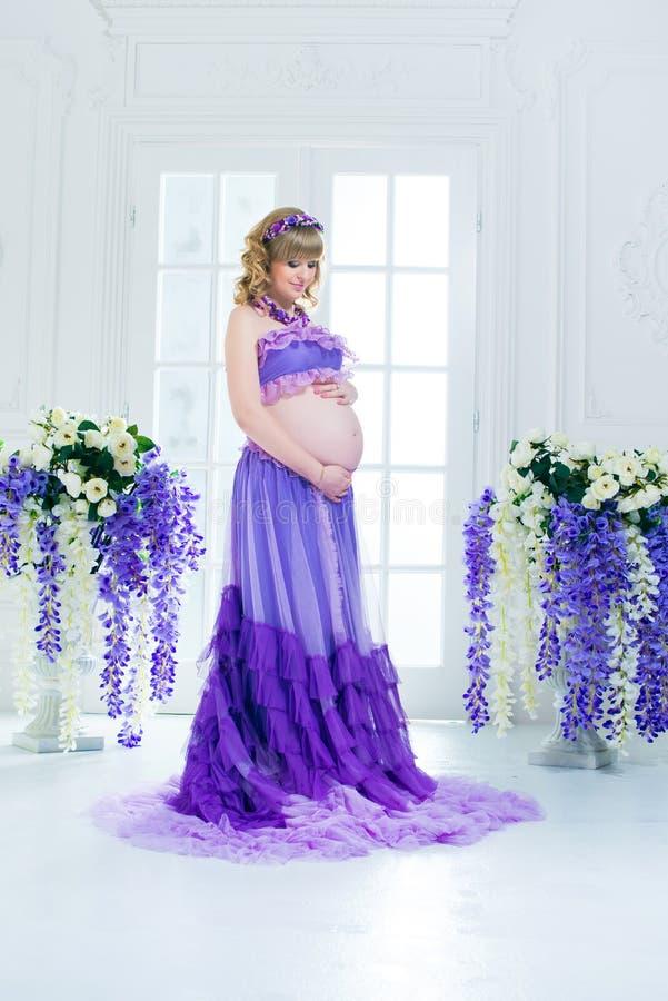 Een gelukkige zwangere vrouw in een purpere lange rok stelt in de studio tegen een achtergrond van bloemen royalty-vrije stock foto's