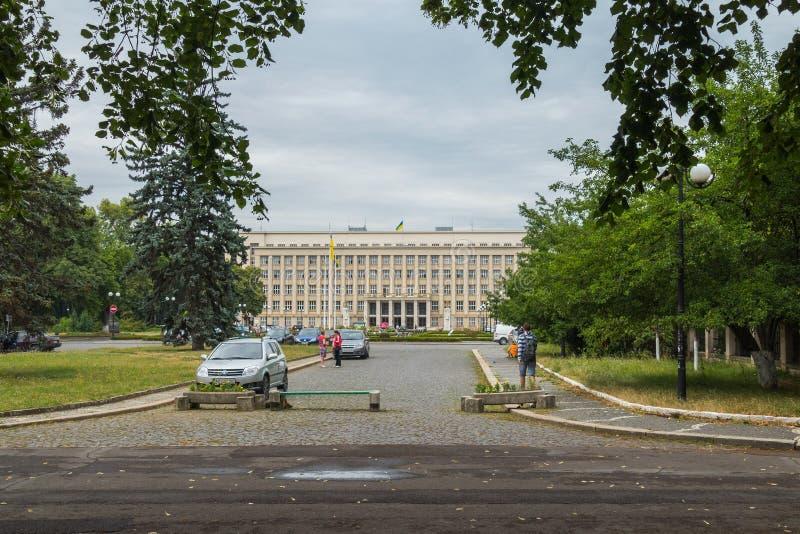 Een gemeentelijk gebouw met een vlag van het land die die in de afstand hangen in de stadslijn wordt gevestigd stock afbeelding