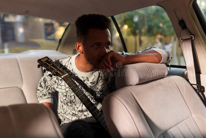 Een gemengde rasmens in salon van auto, met gitaar, die emoties hebben Een student die laat op muziekexamen zijn royalty-vrije stock foto