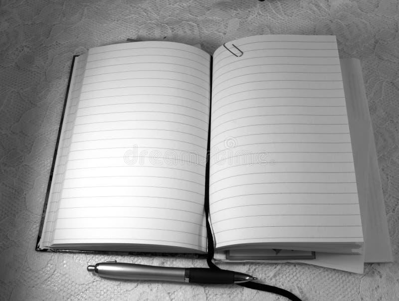 Een geopend agendaboek en een potlood liggen op witte oppervlakte stock foto