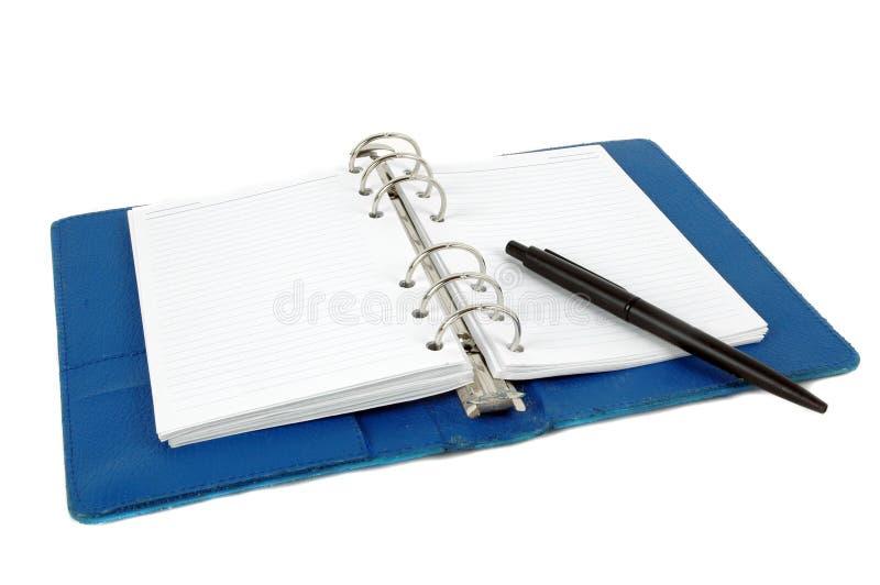 Een geopend blauw leernotitieboekje en een zwarte pen stock fotografie