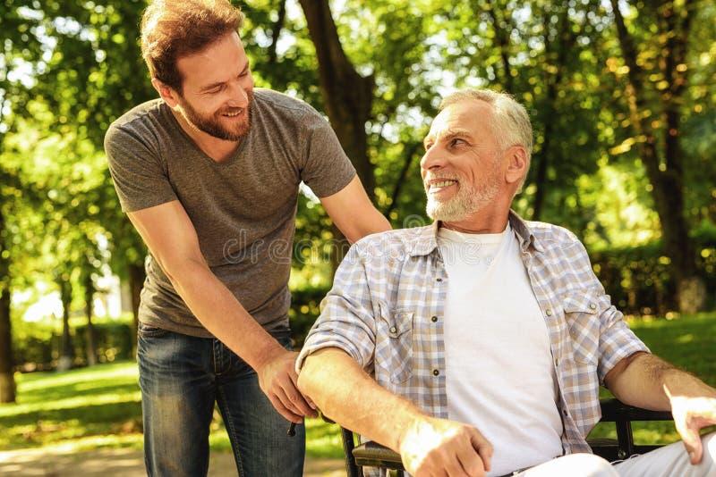 Een gepensioneerde op een rolstoel en zijn volwassen zoon lopen rond het park Zij zijn gelukkig en hebben pret stock foto's