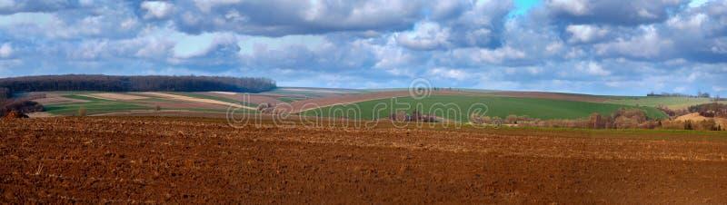 Een geploegd land met een agrarisch landschap van de lente met mooie cloudly hemel royalty-vrije stock foto's