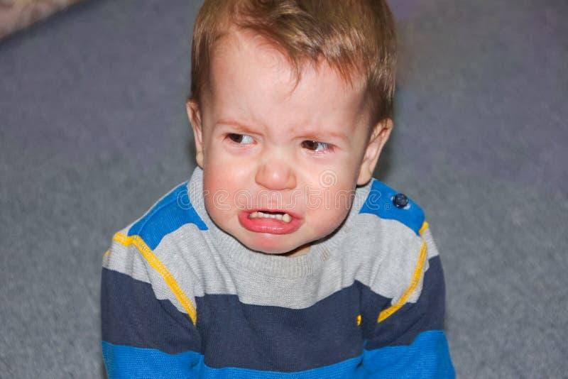 Een geraspt en gekwetst kind zit op de vloer De kleine gepruilde jongen stock foto's