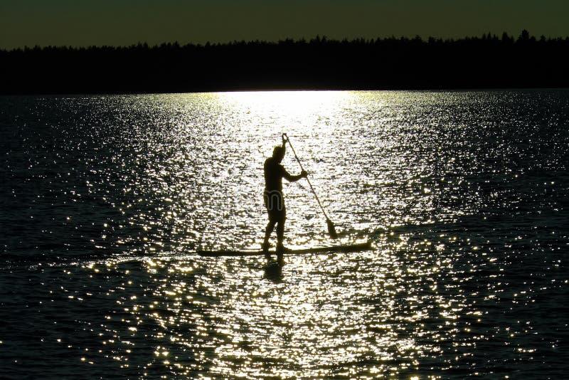 Een gesilhouetteerde mensenpeddel die op een meer van Saskatchewan inschepen stock foto's