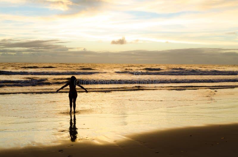 Een gesilhouetteerde vrouw met open wapens dichtbij het overzees op een strand met de zon het toenemen en de zonnestralen die in  stock foto