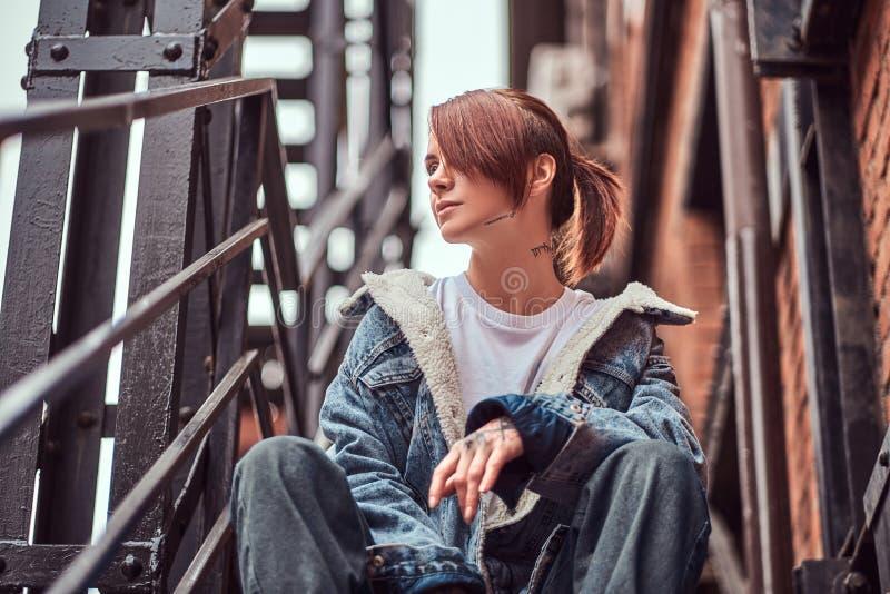 Een getatoeeerd meisje die in kleren dragen die op treden buiten zitten royalty-vrije stock afbeeldingen