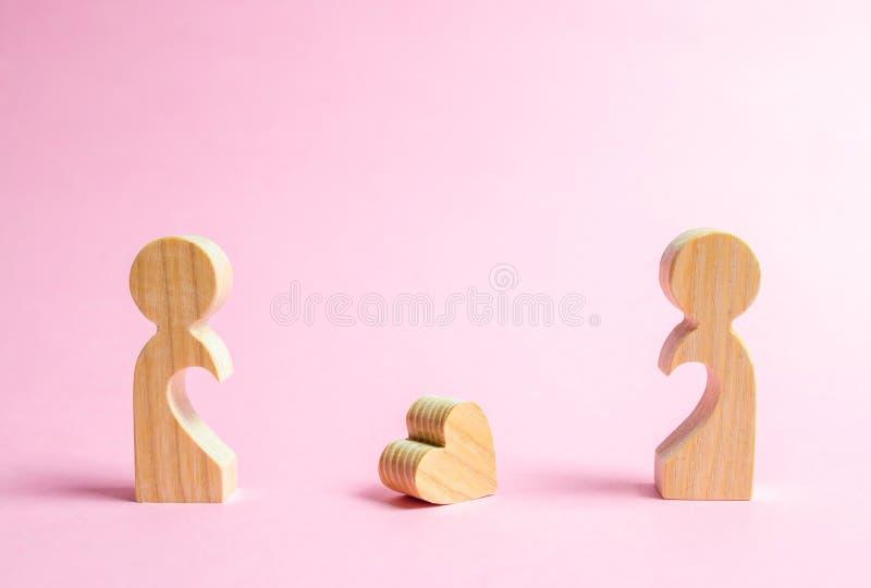 Een gevallen hart ligt tussen twee vroegere minnaars Het concept scheiding of scheiding Bijeenkomst en restauratie van liefdeverh stock foto's