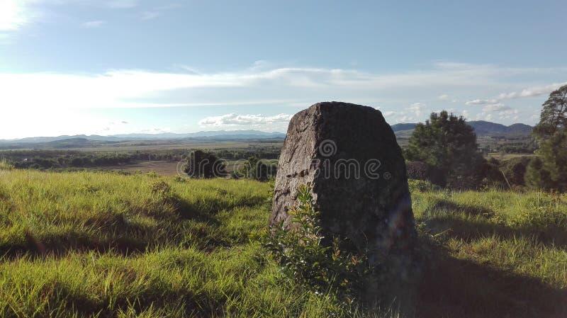 Een gevormde gehouwen steen die zich op een groene weide bevinden stock foto's