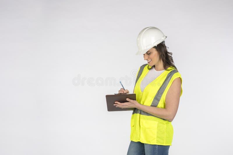 Een geweldige Brunette bouwvakker die tegen een witte achtergrond aankijkt stock afbeelding