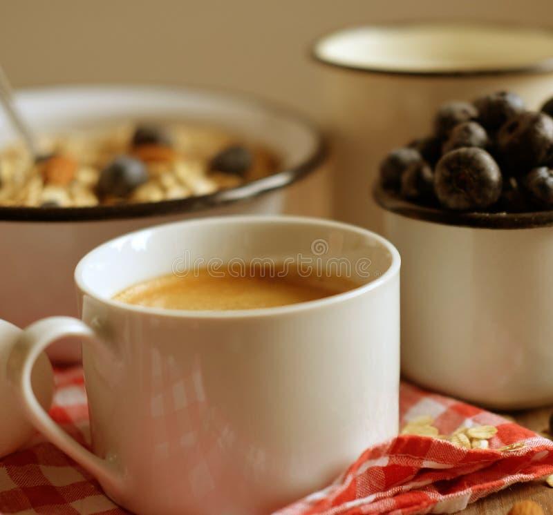 Een gezond ontbijt is een groot begin aan een nieuwe dag Havermeelhavermoutpap, koffie, bessen en noten op een houten lijst royalty-vrije stock afbeelding