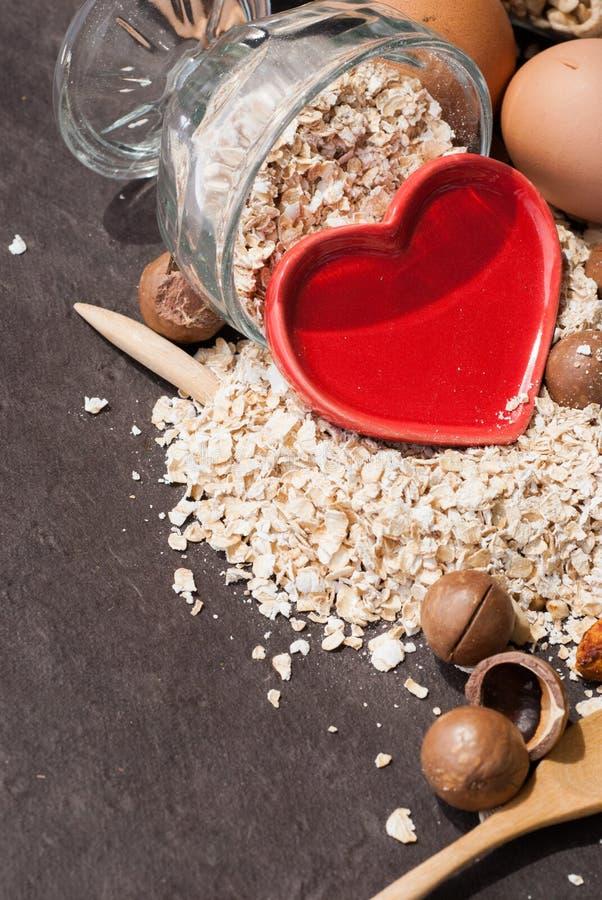 Een Gezonde Droge Havermaaltijd met noot en Rood hart in een houten lepel stock afbeelding