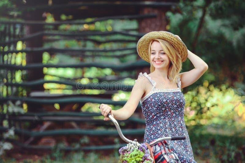 Een gezonde vrouw Het modelmeisje van de schoonheidszomer met de het heldere bos en mand van de kleurenfiets stijlvrije tijd Een  royalty-vrije stock afbeelding