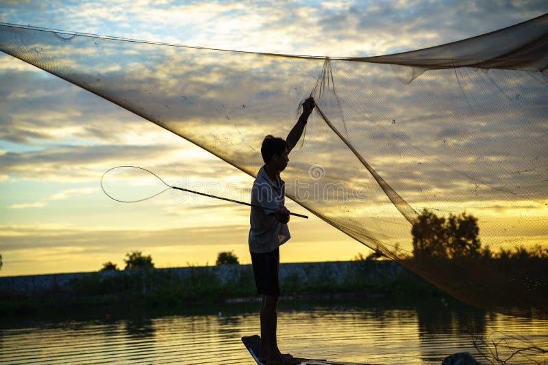 Een Giang, Vietnam - 6 Dec, 2016: Vissers schoonmakend visnet op het gecultiveerde gebied van Tha La in een Giang-provincie, Meko royalty-vrije stock fotografie