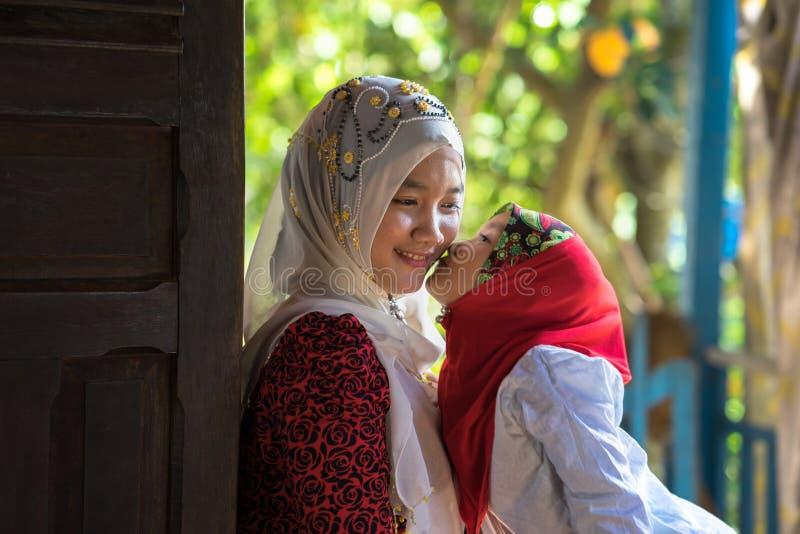 Een Giang, Vietnam - 6 Sep, 2016: Vietnamees moslimmeisje die het traditionele rode kleding spelen met haar zuster in een champad royalty-vrije stock foto's