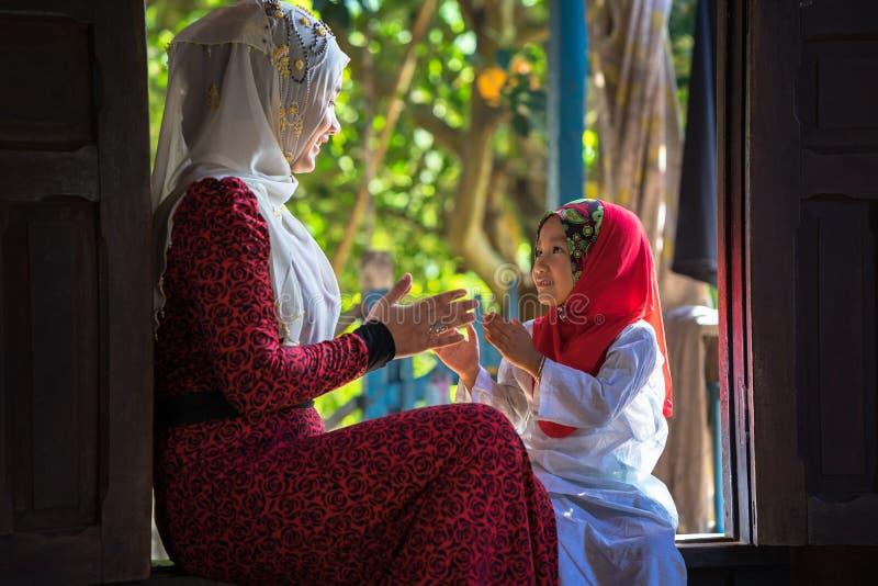 Een Giang, Vietnam - 6 Sep, 2016: Vietnamees moslimmeisje die het traditionele rode kleding spelen met haar zuster in een champad stock foto's