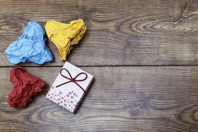 Een gift-doos en Drie kleurrijke hart gevormde verfrommelde documenten op houten lijst Valentine& x27; s Lover& x27; s dag royalty-vrije stock afbeeldingen