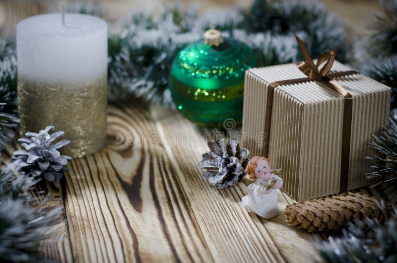 Een gift legt op een houten lijst naast een kaars, kegels en een engel tegen de achtergrond van Kerstmisdecoratie stock fotografie