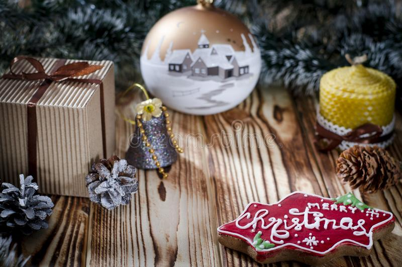 Een gift legt op een houten lijst naast een kaars, kegels en een engel tegen de achtergrond van Kerstmisdecoratie royalty-vrije stock afbeeldingen