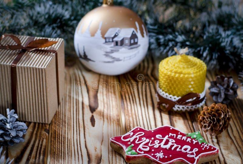 Een gift legt op een houten lijst naast een kaars, kegels en een engel tegen de achtergrond van Kerstmisdecoratie stock foto's