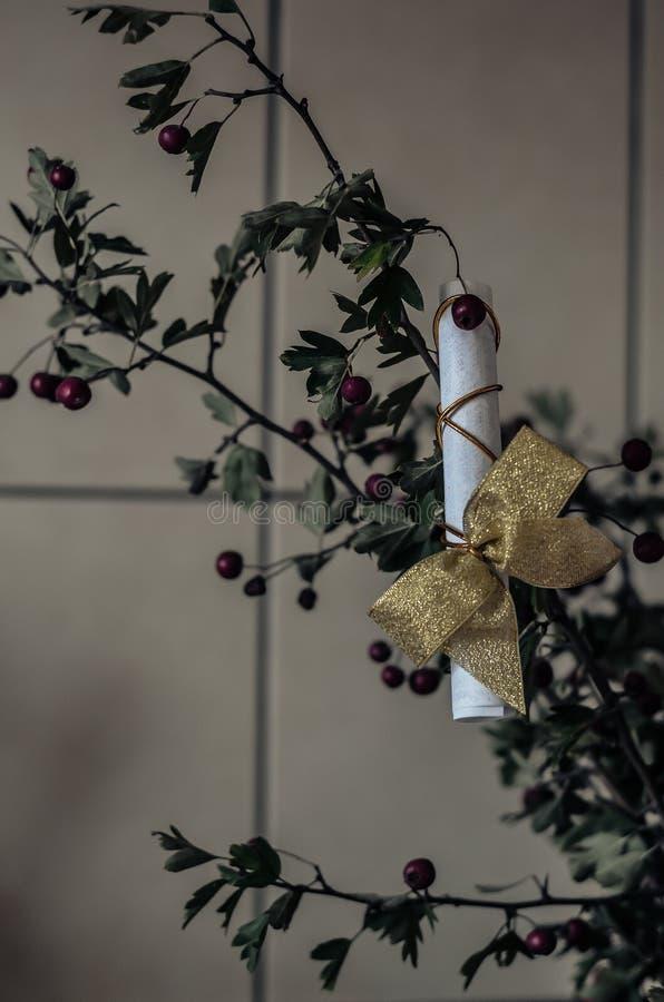Een gift met een gouden boog hangt op een boeket van gescheurde Crataegus van haagdoorntakken Van beneden naar boven het schieten stock afbeeldingen