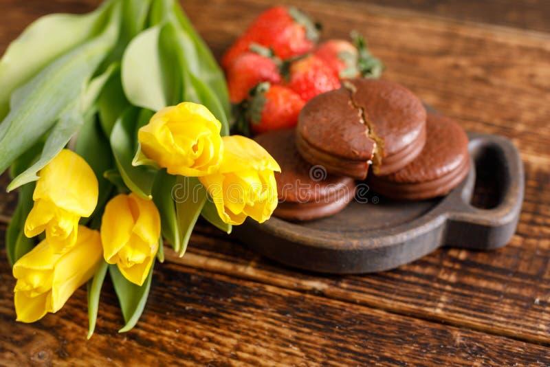Een gift voor de Dag van Valentine ` s Romantisch behandel Gele tulpen, koekjes en aardbeien op een houten lijst Een aardige gift stock fotografie