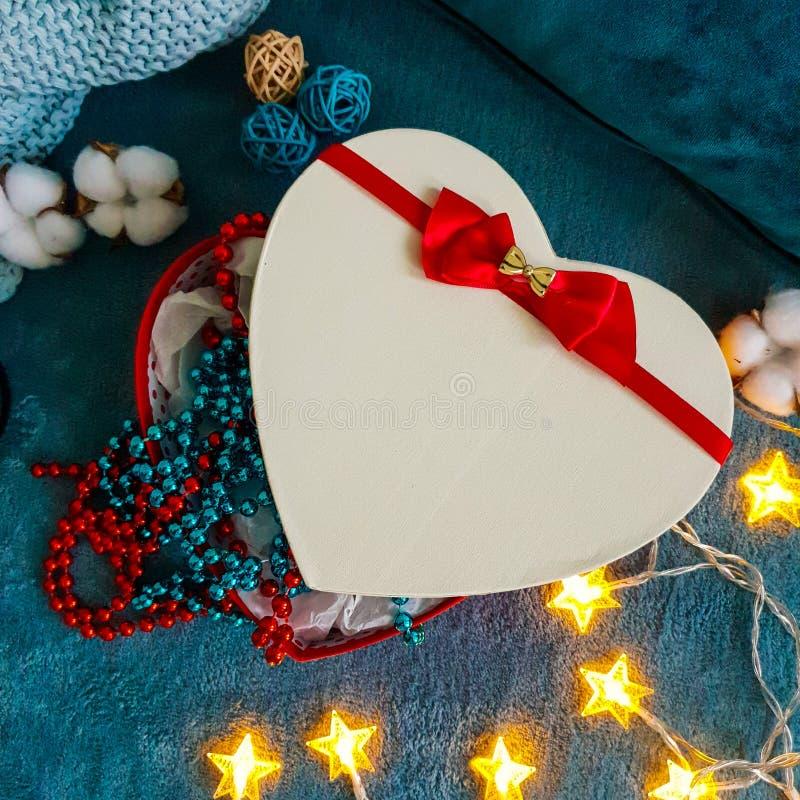 Een giftdoos in de vorm van een hart met een rode boog tegen de achtergrond van comfortabele turkooise die dekens in decoratief k royalty-vrije stock afbeelding