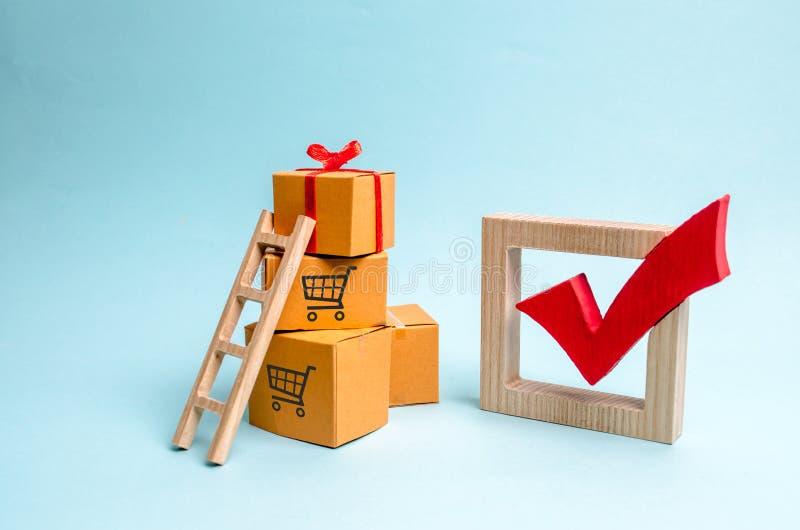 Een giftdoos op een stapel van dozen en een rood vinkje Het concept het vinden van de perfecte gift Het winkelen lijstverkoop, gr stock afbeeldingen