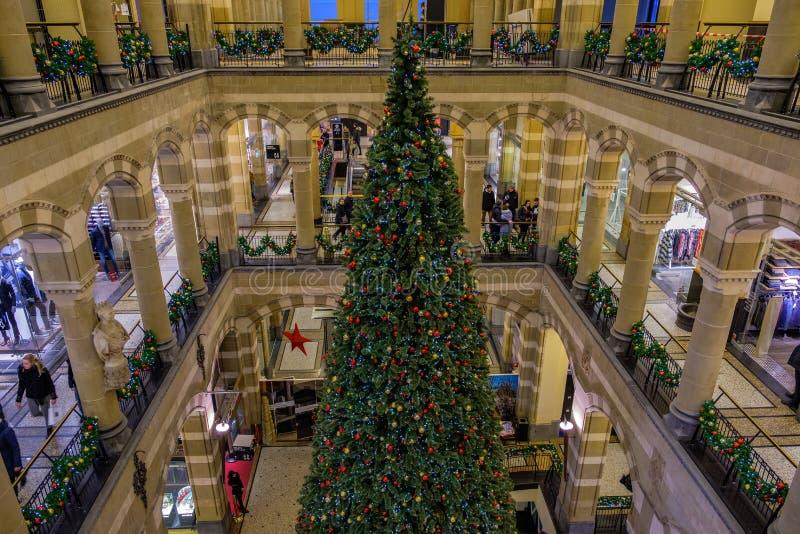 Een gigantische Kerstmisboom kan in het midden van dit mooie winkelende centrum Magna Plaza, Amsterdam, Nederland worden gezien stock afbeeldingen