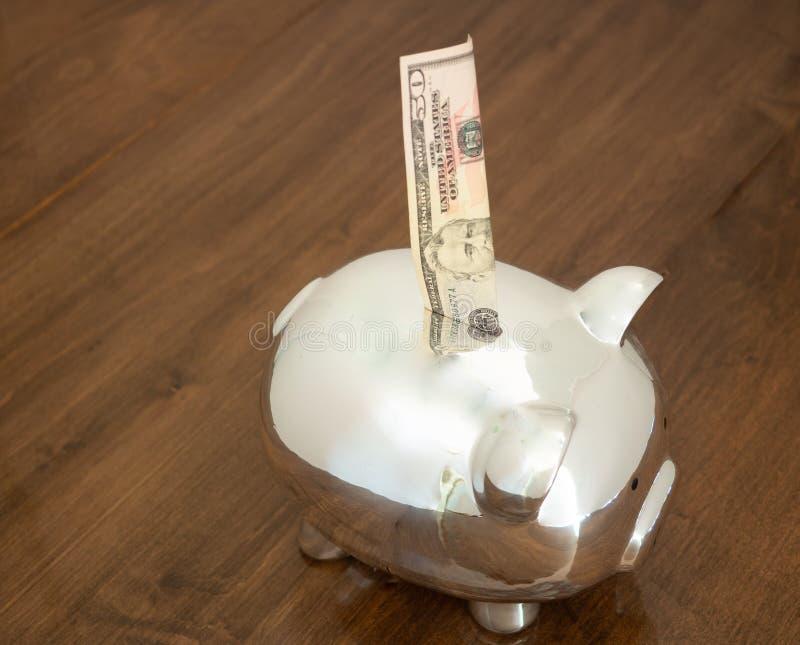 Een Glanzende Piggy-Band met een Vijftig Dollar Bill Being Inserted royalty-vrije stock foto's