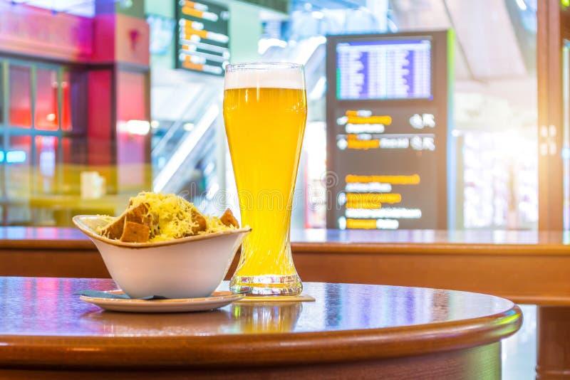 Een glas bier en een plaat van broodkruimels en kaas Op de achtergrond, de online vluchten van raadsvertoningen aan de luchthaven royalty-vrije stock afbeelding