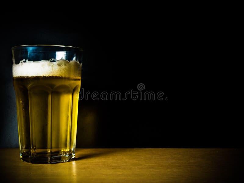Een glas bier op zwarte achtergrond stock afbeelding