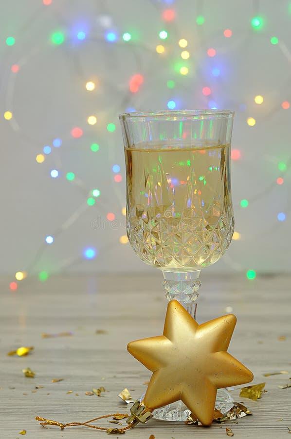 Een glas champagne met een gouden decoratie die van de Kerstmisboom van de stervorm wordt getoond stock foto