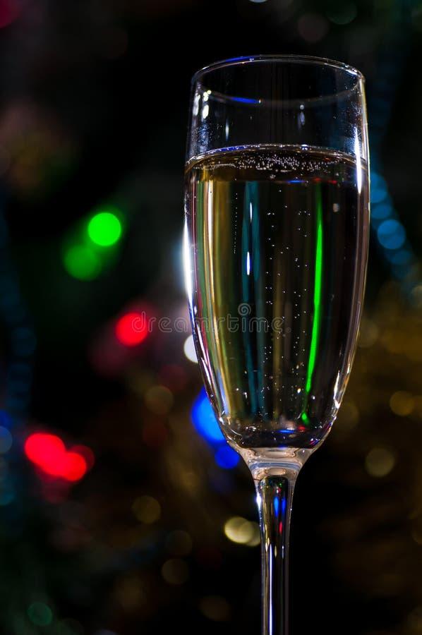 Een glas champagne onder de Kerstboom op een donkere achtergrond stock foto's