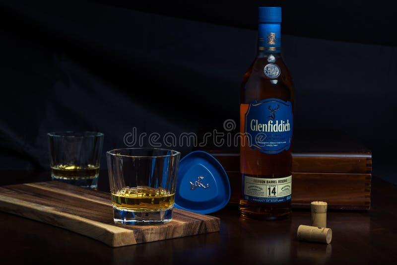 Een glas en een fles Schotse wisky op een rozehoutlijst stock fotografie