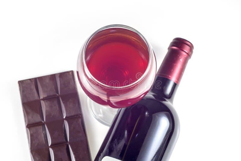 Een glas, een fles rode wijn, een reep chocolade op een witte achtergrond royalty-vrije stock afbeelding