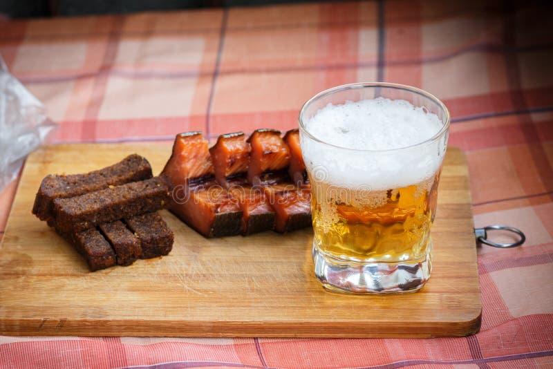 Een glas licht bier met gerookte vissen en zwart gebraden brood in knoflook Bier en biersnack op een houten Raad stock afbeelding
