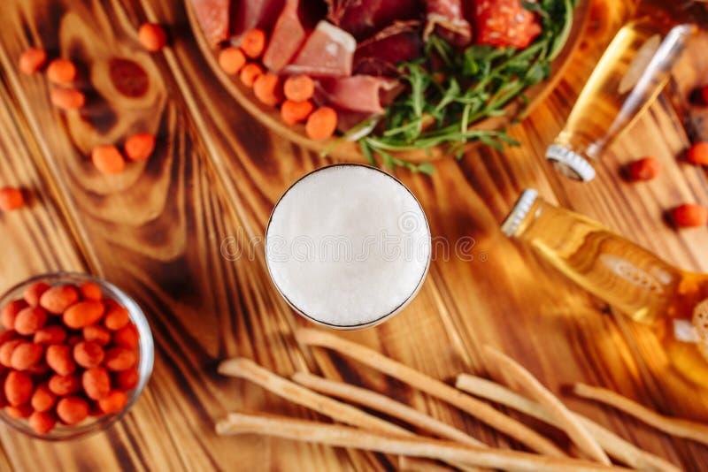 Een glas licht bier Bier met vleesvoorgerechten Gerookt vlees en met een laag bedekte knapperige pinda's, broodstokken Schokkerig stock foto