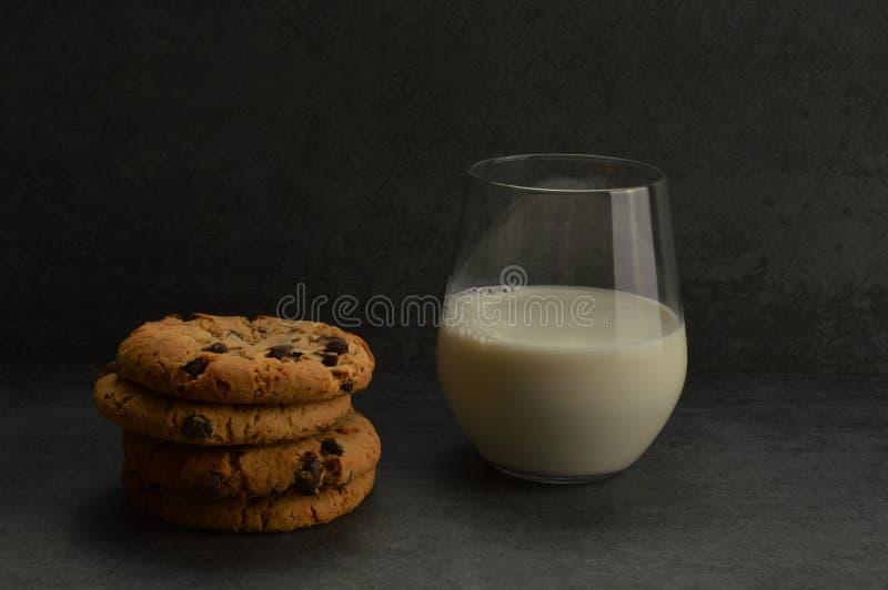 Een glas melk en chocoladekoekjes op de grijze rustieke steenachtergrond royalty-vrije stock foto